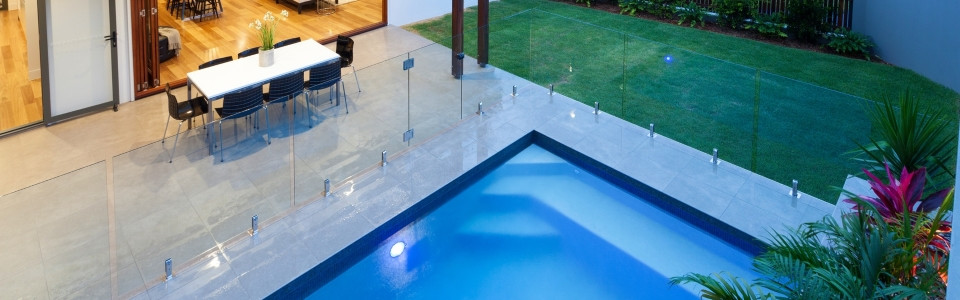 Luxury home with swimming pool and frameless glass pool fencing at dusk