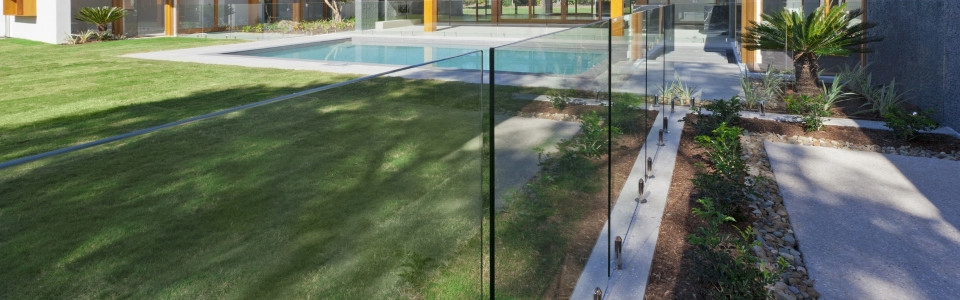Modern backyard with swimming pool with frameless glass pool fencing in mansion