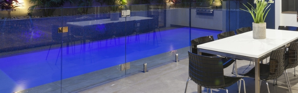 Modern backyard with swimming pool and bbq area with frameless glass pool fencing